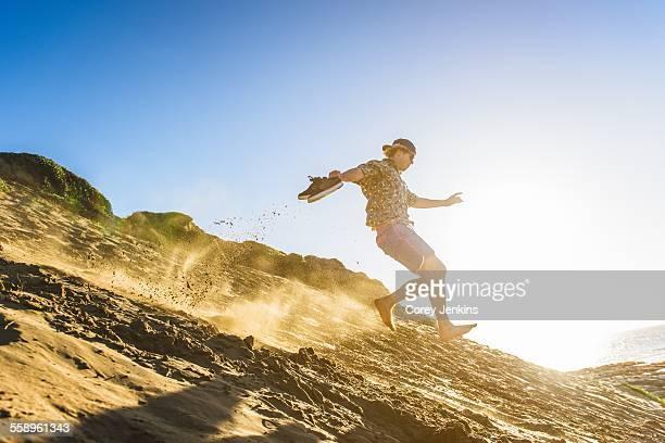 Young man running down sandy hill