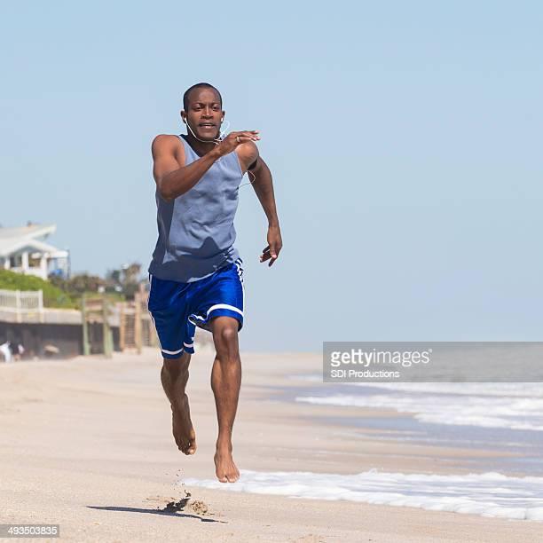 Jeune homme courir vite sur la plage