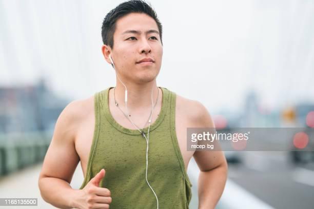 giovane che corre in città - canotta foto e immagini stock