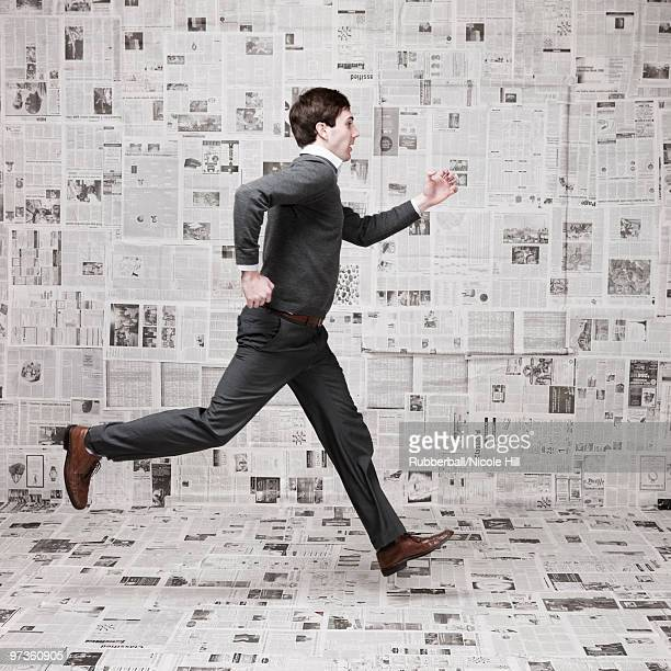 Young man running in front of wall covered with newspapers