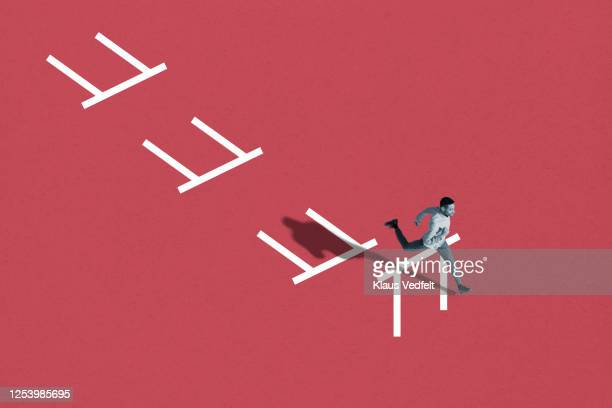young man running in hurdle race - hurdling track event stock pictures, royalty-free photos & images