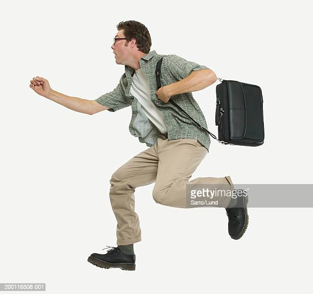 Young man running in mid air with laptop case, side view