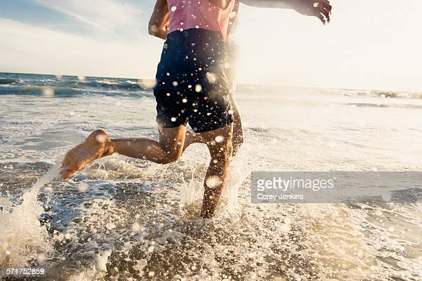 Young man running in sea, low section