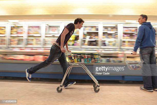 Young man running in supermarket with trolly