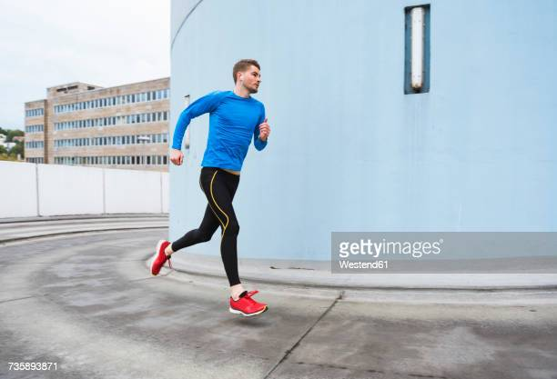 young man running in the city - jogging stock photos and pictures