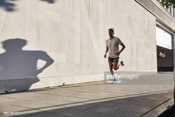 young man running in the city - bewegung stock-fotos und bilder