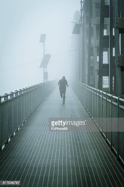 Junger Mann läuft im Nebel auf Iron Bridge