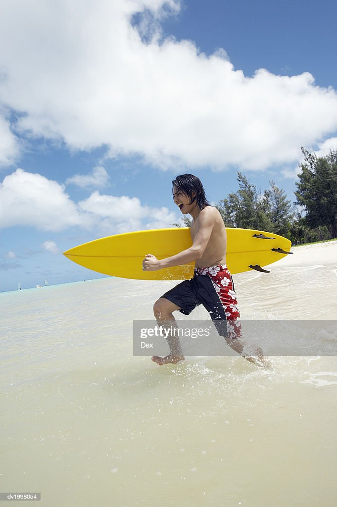 Young Man Running in the Sea and Carrying a Windsurfing Board : Stock Photo