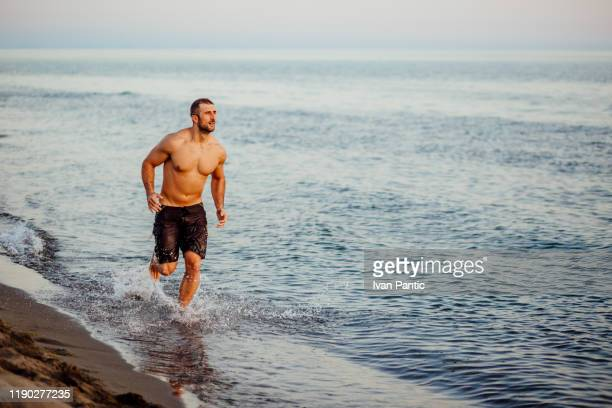 young man running on a beach - swimwear stock pictures, royalty-free photos & images