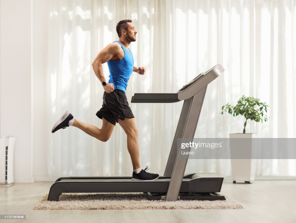 Junger Mann läuft zu Hause auf einem Laufband : Stock-Foto