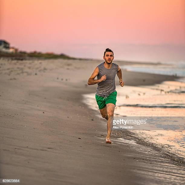 Young man running on Hampton Beach, Long Island, USA