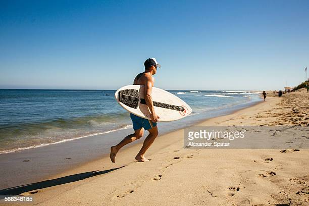 Young man running on the beach holding his surfboard Malibu Los Angeles California USA