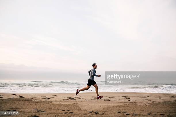 young man running on the beach - carrera fotografías e imágenes de stock