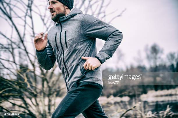 young man running on the field - running stock pictures, royalty-free photos & images