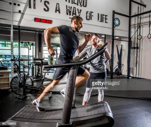 若い男は、フィットネス インストラクター動機彼ながらトレッドミルで実行されています。 - コーチ ストックフォトと画像