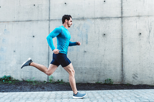 Young man running outdoors in morning 1125038961