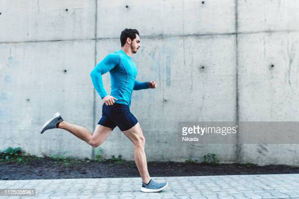 young man running outdoors in morning - lopes stock pictures, royalty-free photos & images