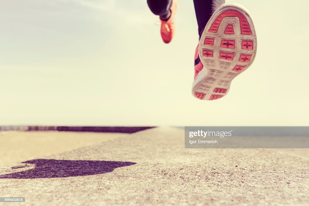 Young man running outdoors, mid air, low section : Stock Photo