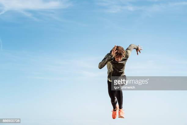 Young man running outdoors, mid air