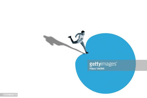 young man running over blue blob shape - jumping stock pictures, royalty-free photos & images