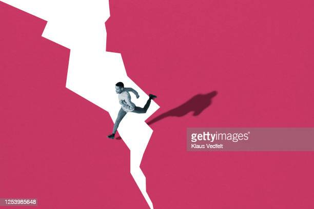 young man running over cracked colored background - zweifarbig farbe stock-fotos und bilder