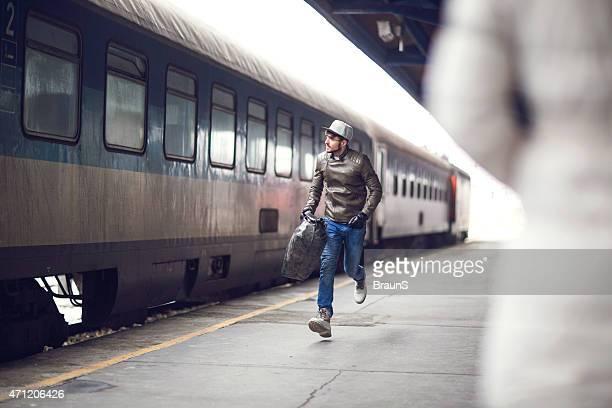 Joven corriendo a tomar el tren.