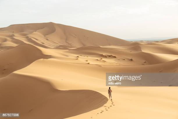 a young man running to the beyond - merzouga stock pictures, royalty-free photos & images