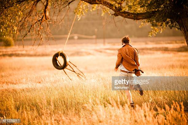 Jeune homme jogging vers une Corde pour se balancer