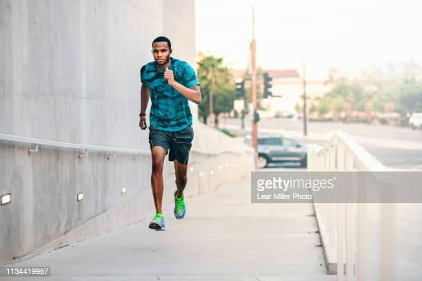 young man running up city footbridge - のぼり ストックフォトと画像