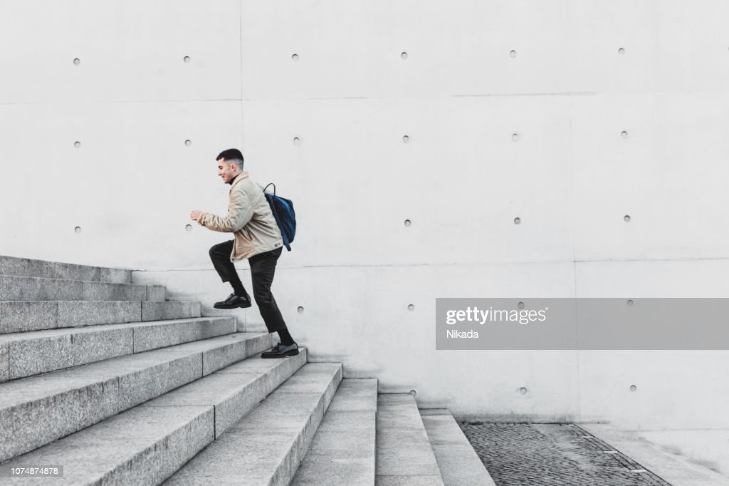 Young man running up steps in urban setting : Stock Photo