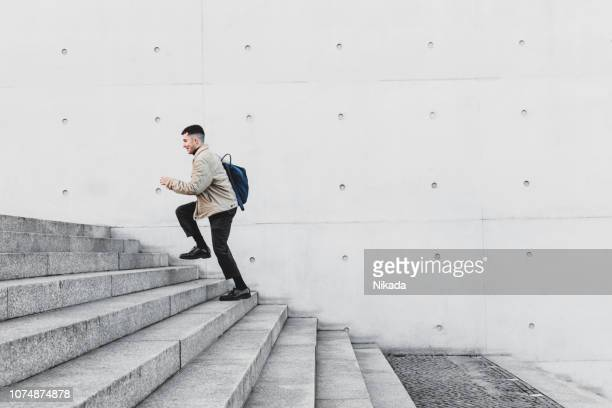young man running up steps in urban setting - staircase stock pictures, royalty-free photos & images