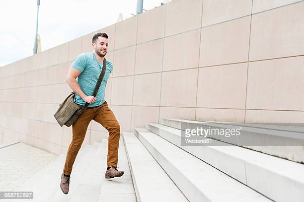 young man running upstairs - stufen stock-fotos und bilder
