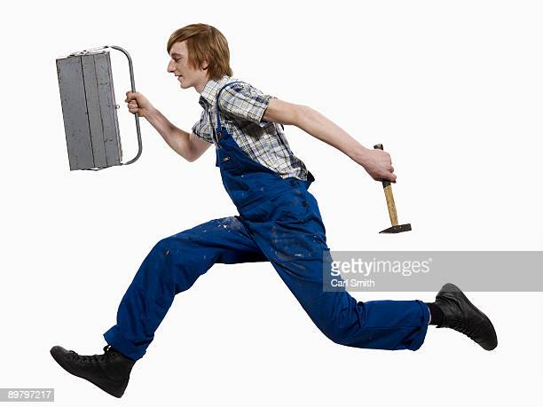 A young man running with a toolbox and hammer