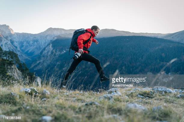 young man runs along mountain ridge at sunrise - jacket stock pictures, royalty-free photos & images