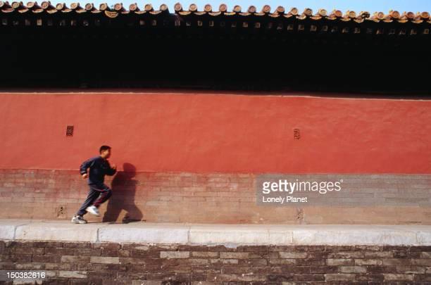 A young man runs along the red walls of Beijing's Forbidden City.