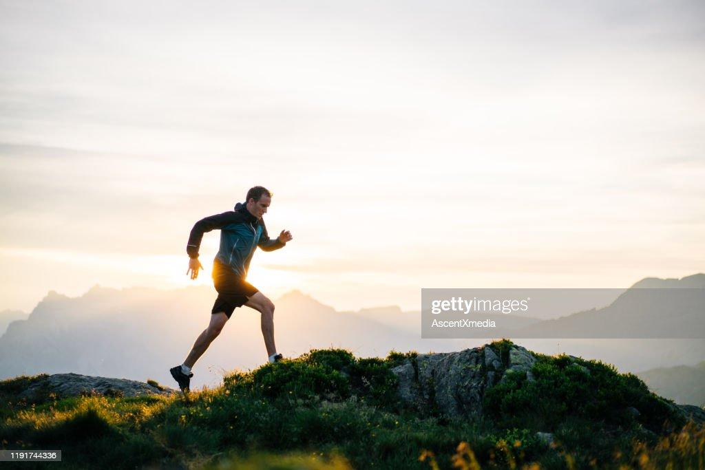 Young man runs on mountain ridge at sunrise : Stock Photo