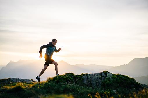 Young man runs on mountain ridge at sunrise 1191744336