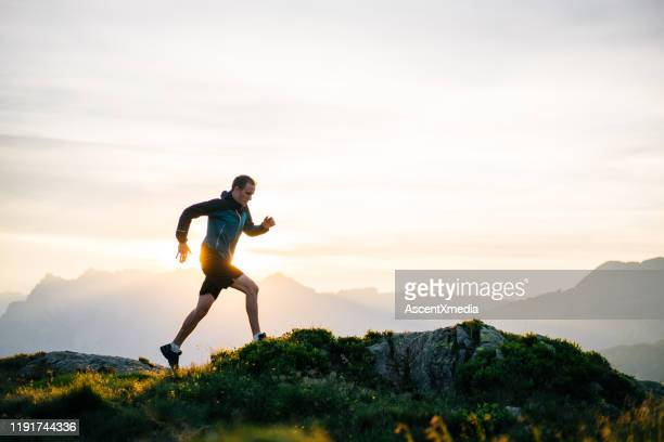 young man runs on mountain ridge at sunrise - wellbeing stock pictures, royalty-free photos & images
