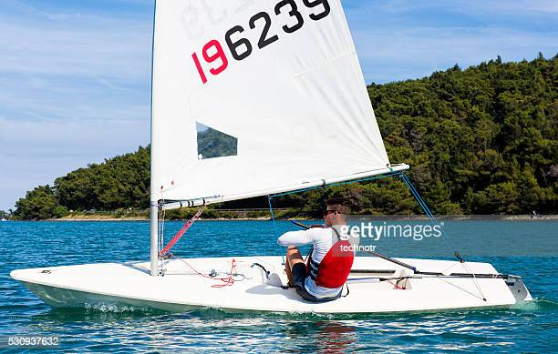 Young man sails a laser class sailing boat