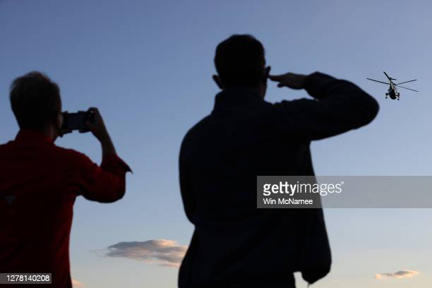 Young man salutes as Marine One, the presidential helicopter, carries U.S. President Donald Trump from the White House to Walter Reed National...