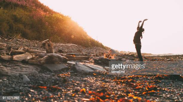 young man saluting a fire on the beach. vacations at the sea. sunset. gaspesie, quebec, canada - gaspe peninsula stock pictures, royalty-free photos & images