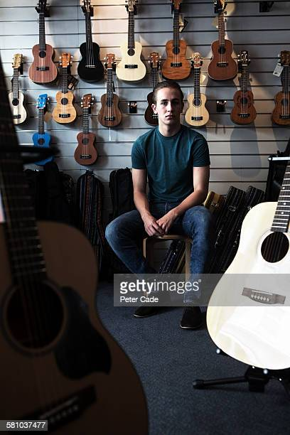 Young man sat in music shop