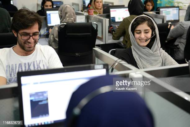 A young man sat next to a woman in veil smile while working in the operation room of Snapp online taxi service on April 8 2018 in Tehran Iran Snapp...
