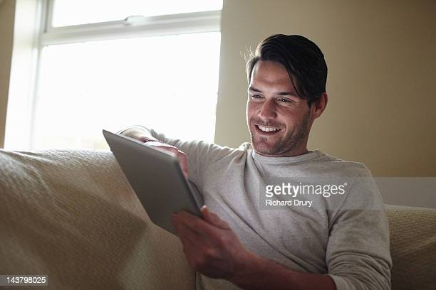young man sat on sofa using digital tablet - richard drury stock pictures, royalty-free photos & images