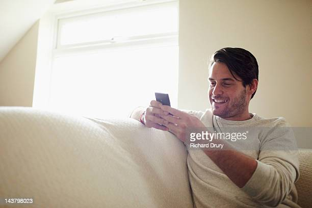 young man sat on sofa using mobile phone - richard drury stock pictures, royalty-free photos & images