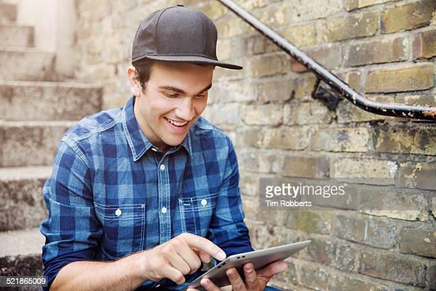 young man sat on steps with tablet. - berretto da baseball foto e immagini stock