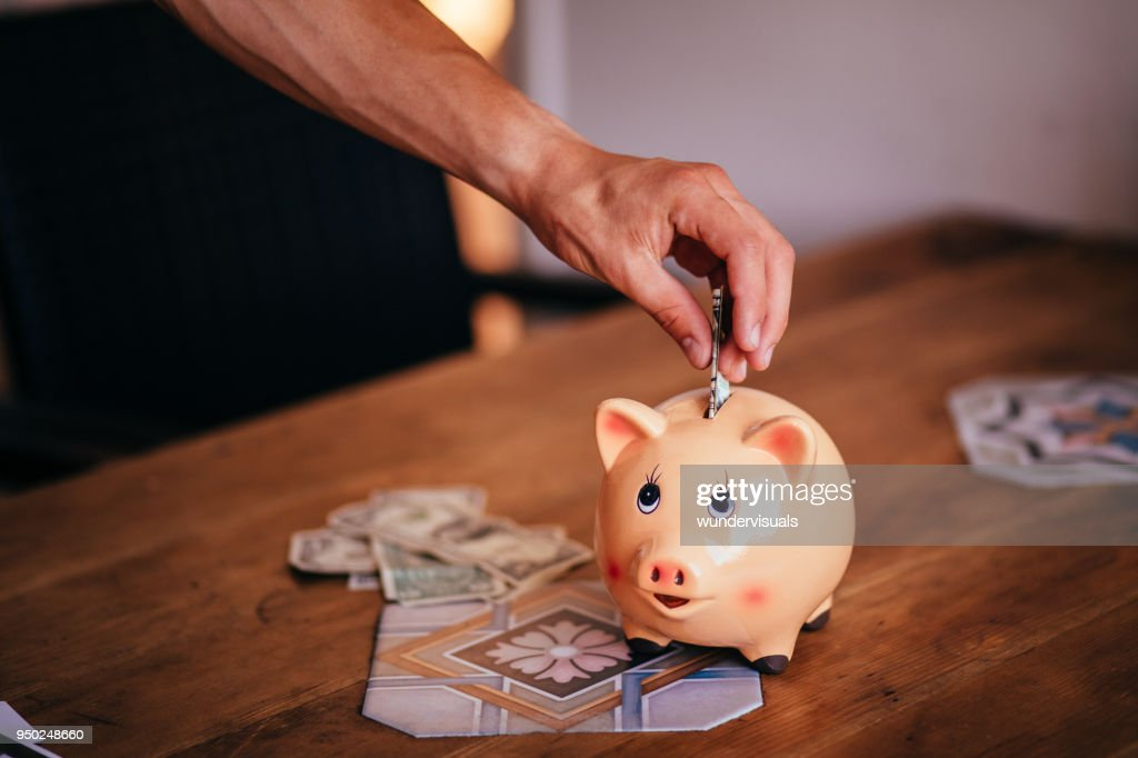 Young man saving money in a piggy bank at home : Stock Photo