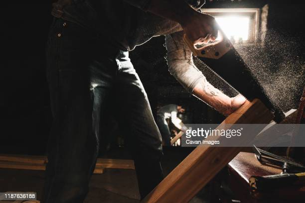 young man saws wood in workshop - toughness stock pictures, royalty-free photos & images
