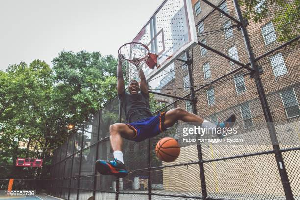 young man scoring goal at basketball court - black photos et images de collection