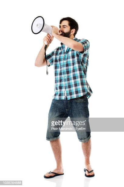 young man screaming in megaphone while standing against white background - サンダル ストックフォトと画像